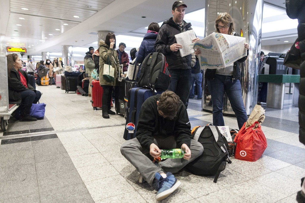 People wait for their delayed flights at LaGuardia Airport in New York